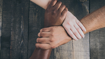 hands of three different people from different backgrounds interlocked