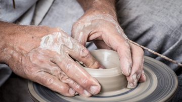 Hands working to shape clay on a potter's wheel